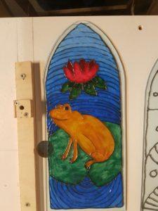 Fensterscheibe mit Frosch und Seerose