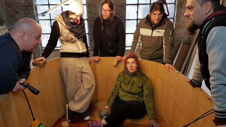 Die Gruppe sitzt und steht im abgesägten Zuber