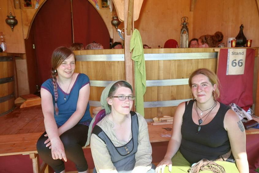 Badezuber mit Badegästen und drei Frauen vor dem Badehaus auf der Zuberstufe sitzend