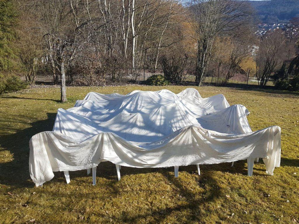 Zeltdach auf Gartenstühlen zum Trocknen ausgebreitet