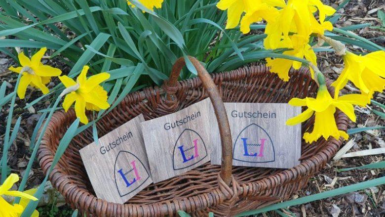 Weidenkorb mit Gutscheinen unter Osterglocken